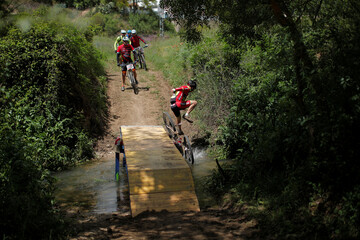 A mountain biker falls as he crosses a river while participating in the cycling category of the XIX 101km international competition in Ronda