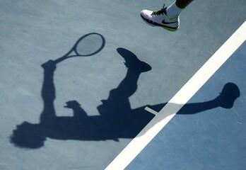 Switzerland's Federer casts a shadow as he serves during his quarter-final match against Czech Republic's Berdych at the Australian Open tennis tournament at Melbourne Park