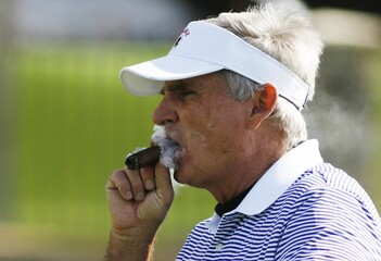James Dunne smokes a cigar on the 14th hole during the final round of the Pebble Beach Pro-Am golf tournament