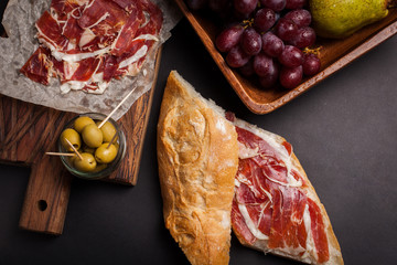 Jamon Iberico with white bread, olives on toothpicks and fruit on a dark background. Top view