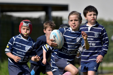 Olivia Schelkens, 7 years old and the only girl in her team, runs with the ball during the rugby youth finals in Dendermonde