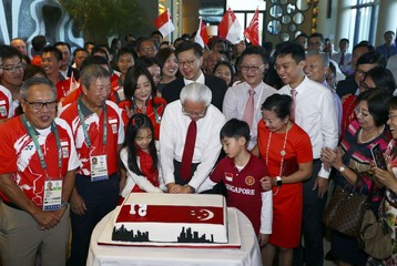 Singapore's President Tony Tan cuts a cake during the Singapore National Day Reception in Rio de Janeiro