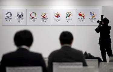 A photographer takes pictures of the four shortlisted emblem designs for the Tokyo 2020 Olympic and Paralympic Games as journalists sit behind nearby, after the designs were unveiled in Tokyo, Japan