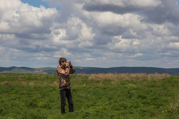 Photographer at the steppe in Kazakhstan. Amazing cloudy sky