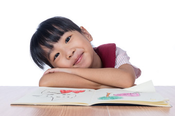 Asian Little Chinese girl reading a painting book