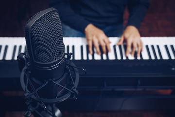 condenser microphone on male musician hands playing piano background