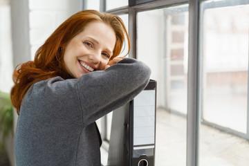 frau stützt sich lächeln auf einen aktenordner