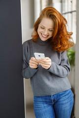 lächelnde frau tippt eine nachricht auf ihrem mobiltelefon