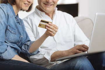 Mature Couple connected with laptop and shopping online