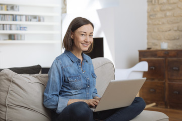 Attractive mature woman using a laptop while relaxing on a sofa at home