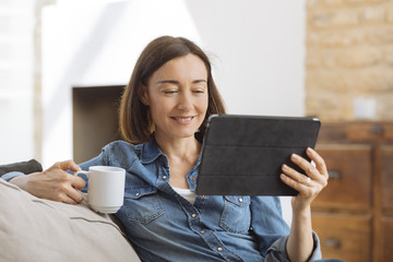 Mature woman using tablet computer while relaxing on sofa at home