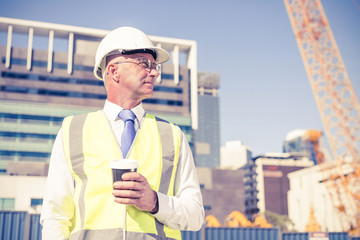 Engineer builder on construction site at sunny day with coffee i