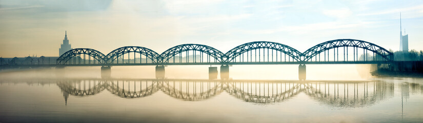 Silhouette of Riga Railway bridge in foggy early morning
