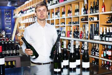 Cheerful man buying bottle of wine