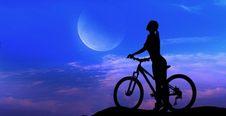 Crescent moon with beautiful sunset background . Dawn cloud .  Sunset or sunrise with clouds, light rays and other atmospheric effect . Silhouette of the young sports girl