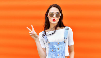 Beautiful brunette woman in sunglasses blowing lips kiss over orange background.  Outdoors. Young  woman. Street fashion. Red lipstick.