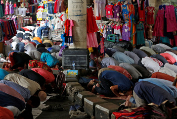Muslim labourers and shop keepers pray at the entrance to a parking garage near a crowded mosque during Friday prayers at Tanah Abang Textile Market in Jakarta