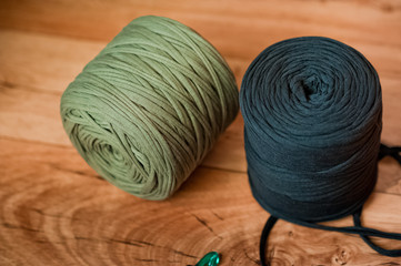 Knitted yarn in large spools. Black and green, olive yarn on a wooden background