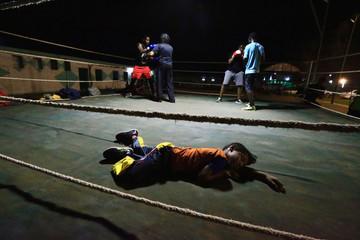 A boy sleeps inside the ring as Arafat Abkar, 22, practises boxing at Nile Club in Khartoum