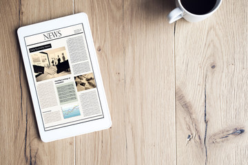 Newspaper on digital tablet on wooden table