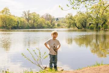 Little boy standing near the pond summer
