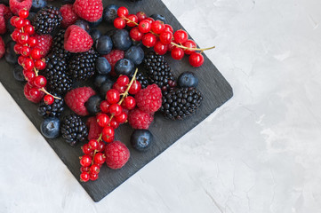Mix of berries raspberries red currants blueberries and blackberries on black slate board. White stone background.  Overhead view and copy space