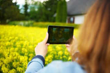 A young woman makes selfie in canola field
