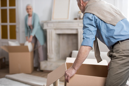 side view of man holding cardboard box and helping wife unpack things