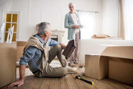 low angle view of smiling woman having discussion with husband at new home