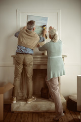 rear view of senior husband and wife hanging picture on wall over the fireplace