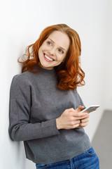 lächelnde frau mit roten locken schreibt eine sms