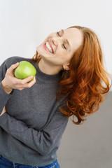 lachende frau hält einen grünen apfel in der hand