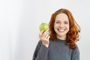 frau zeigt einen leckeren grünen apfel