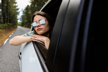 Stylish girl looking out of car window