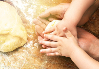 Hands of father and baby son together kneading the dough