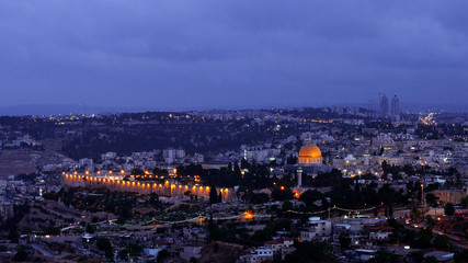 Night falls on Jerusalem city. Citylights light up at night while sunset goes over Jerusalem Dome of the Rock and Al Aqsa mosque.