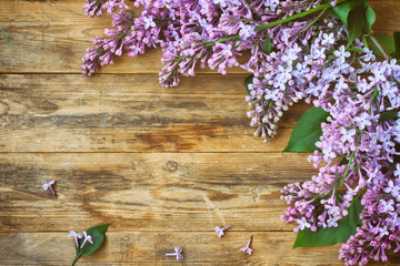 Branches of a blossoming purple lilac, on old wooden table