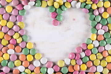 Heart shape above wooden table with colorful round candies arround