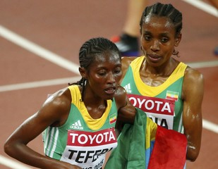 Ethiopia's Genzebe Dibaba helps her compatriot Senbere Teferi (L) when she gets sick after finishing the women's 5,000 metres final during the 15th IAAF World Championships at the National Stadium in Beijing