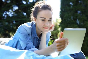 Fototapeta Wakacyjne lenistwo na łonie natury. Piękna, młoda kobieta wypoczywa czytając tablet siedząc na kocu obraz