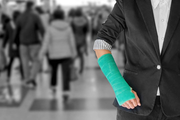 Injury businesswoman with green cast on hand and arm on blurred background airport