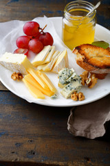 Cheese plate with grapes, honey, bread and walnuts on old wooden table