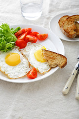 Fried Eggs with tomato, lettuce, bread and water glass