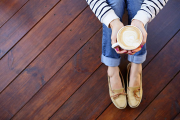 Woman holding in hands cup of coffee with milk sitting on the floor