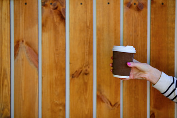 Coffee to go. Disposable cup in woman hand