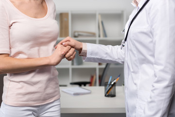cropped view of doctor with stethoscope and patient holding hands in professional clinic