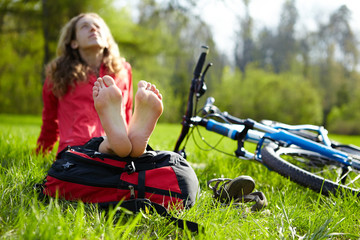 Happy girl cyclist enjoying relaxation sitting barefoot in spring park