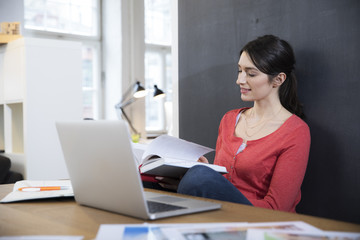 Woman with book and laptop at desk in office