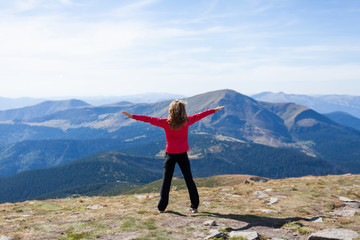 Hiker standing on a peak over the mountain with raised hands