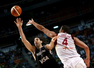 Argentina's Luis Scola jumps for the ball with Venezuela Miguel Marriaga during their 2015 FIBA Americas Championship final basketball game in Mexico City
